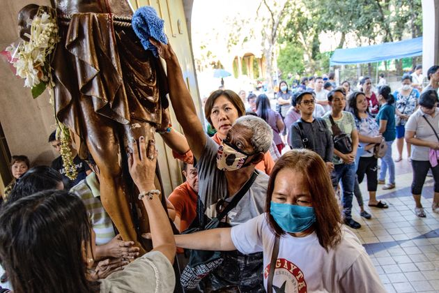 Filipino Catholics wearing protective masks touch an image of Jesus Christ during Ash Wednesday services...