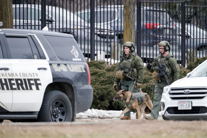 Police conduct searches outside the Molson Coors campus in Milwaukee on Wednesday after reports of a possible shooting.