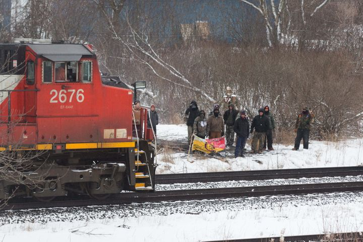 Protesters stand next to the tracks as a CN train moves through Tyendinaga Mohawk Territory, near Belleville, Ont., on Feb. 26, 2020.