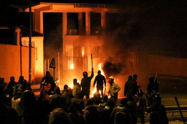 Διαδηλωτές συγκρούονται με αστυνομικούς έξω από το στρατόπεδο στο Παγάνι της Λέσβου, στις 26 Φεβρουαρίου 2020. Το Γαλλικό Πρακτορείο μετέδωσε σχολιάζοντας αυτή τη φωτογραφία, ότι εκατοντάδες διαδηλωτές πέταξαν πέτρες σε αστυνομικούς και εκείνοι απάντησαν με πλαστικές σφαίρες, χειροβομβίδες κρότου-λάμψης και δακρυγόνα. (Photo by Manolis LAGOUTARIS / AFP) (Photo by MANOLIS LAGOUTARIS/AFP via Getty Images)