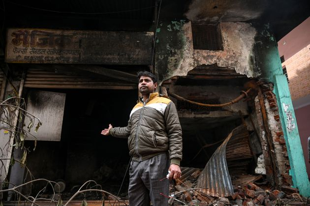 A footwear shop owner in Ashok Nagar shows his burnt
