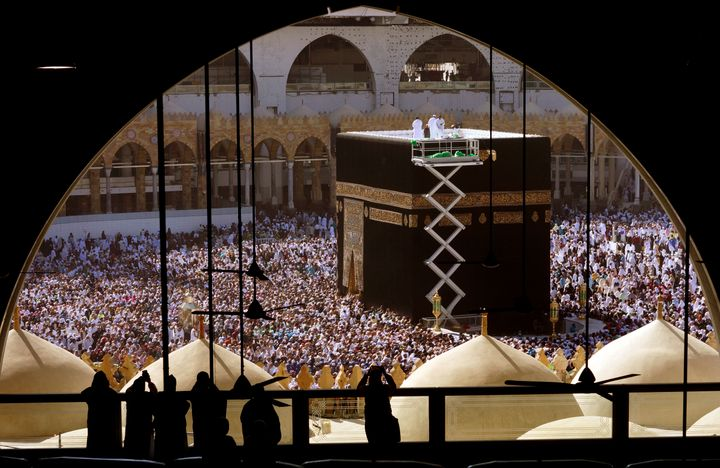 Workers clean the roof of the Kaaba, the cubic building at the Grand Mosque, as worshippers circumambulate around during the minor pilgrimage, known as Umrah in the Muslim holy city of Mecca, Saudi Arabia, Monday, Jan. 27, 2020. (AP Photo/Amr Nabil)