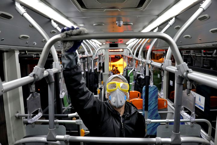 A worker disinfects a public bus against coronavirus in Tehran, Iran, on the early morning of Wednesday, Feb. 26, 2020. (AP Photo/Ebrahim Noroozi)