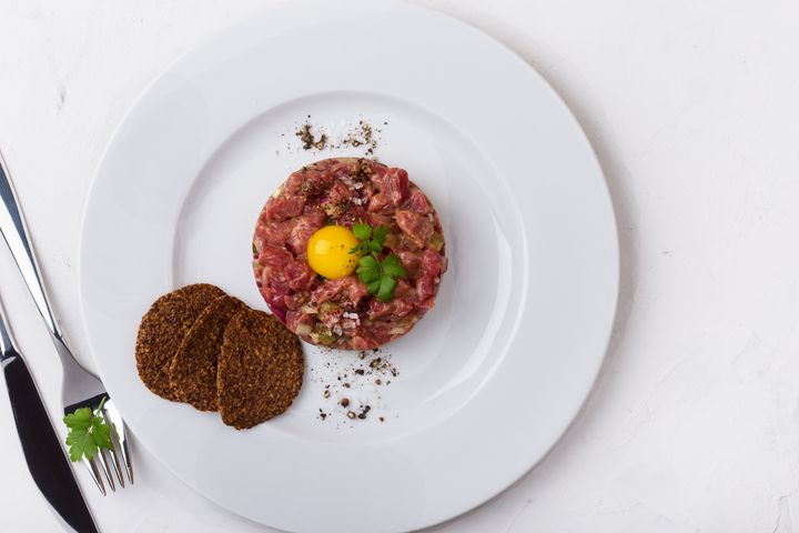 Steak tartare, a popular dish made with raw beef and uncooked egg yolks.