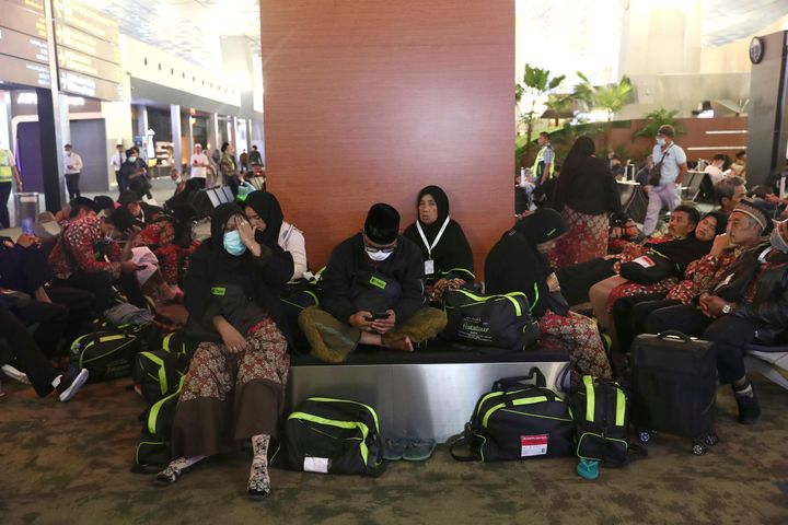 Indonesian who are scheduled to travel to Saudi Arabia for a minor pilgrimage, called 'Umrah', sit at a waiting area as they are turned away from their flights at Soekarno-Hatta International Airport in Tangerang, Indonesia, on Thursday, Feb. 27, 2020. (AP Photo/Tatan Syuflana)
