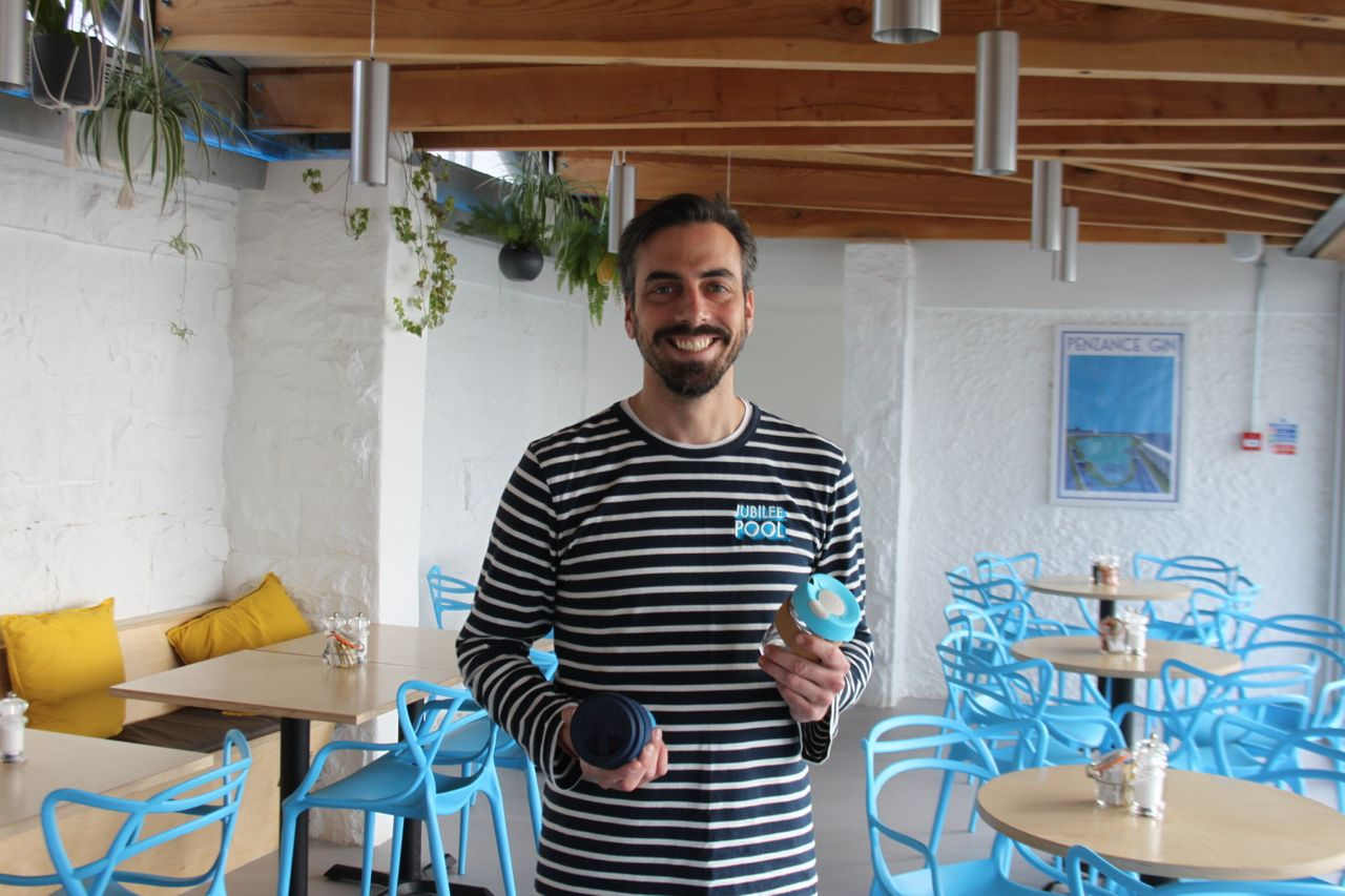 Sam Dean at the Jubilee Café in Penzance with some of the reusable glass coffee cups he sells.