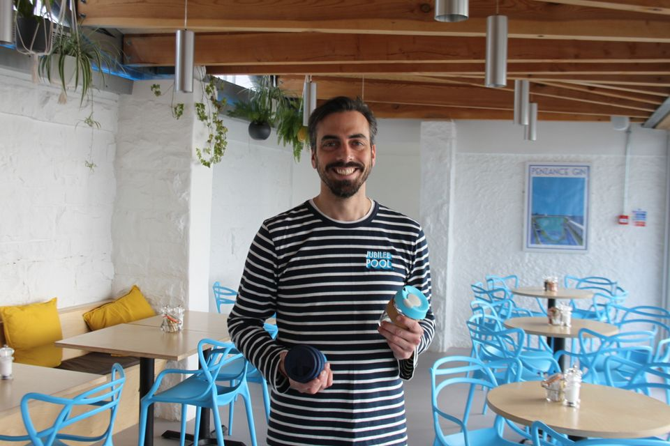 Sam Dean at the Jubilee Café in Penzance with some of the reusable glass coffee cups he