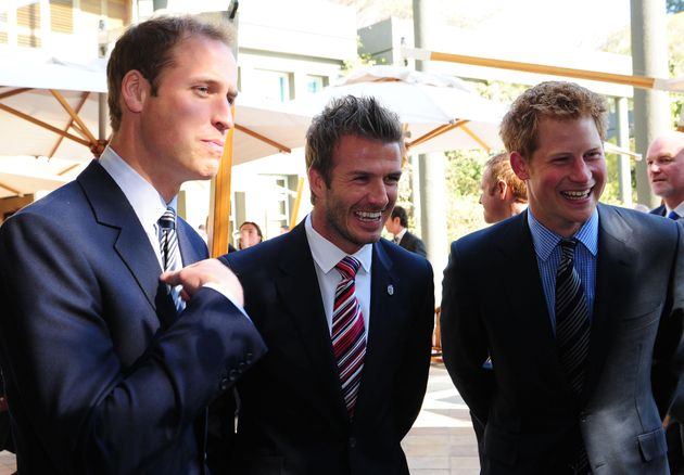 Prince William (left) and Prince Harry flank David Beckham at a reception in Johannesburg onJune...