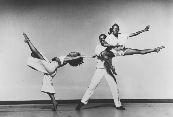 O dançarino moderno Alvin Ailey, ao centro, sobre o palco com duas dançarinas. Nova York, 1975.