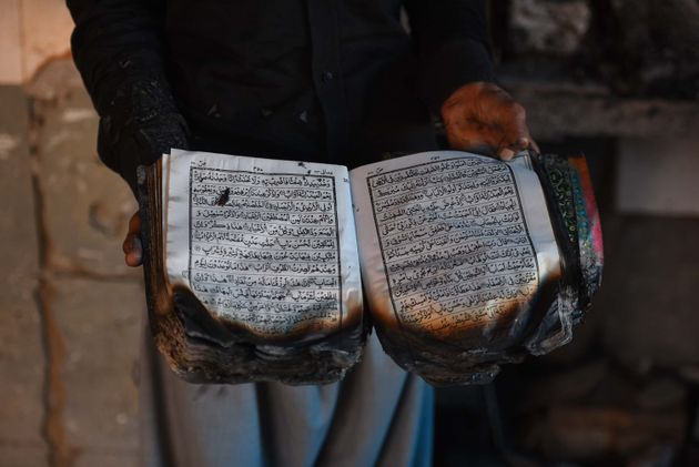 A man holds the holy Quran that was burnt along with the mosque at Mustafabad, on February 26, 2020 in...