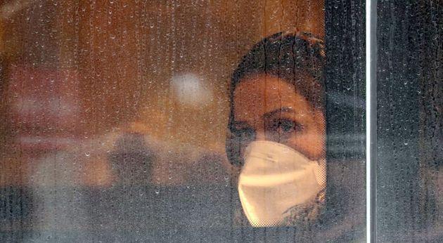 Una mujer con mascarilla observa por la
