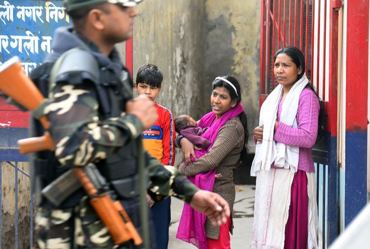 Residents look on as police and paramilitary personnel conduct a patrol in the area between Maujpur and Jaffrabad, on February 26, 2020 in New Delhi.