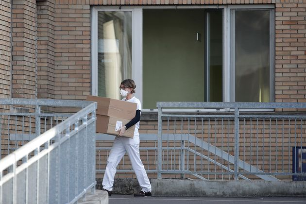 A hospital worker carries boxes into the hospital of Codogno, near Lodi in Northern Italy, Friday, Feb....