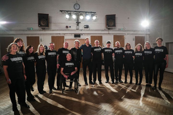 The two pose with members of the Invictus Games Choir.
