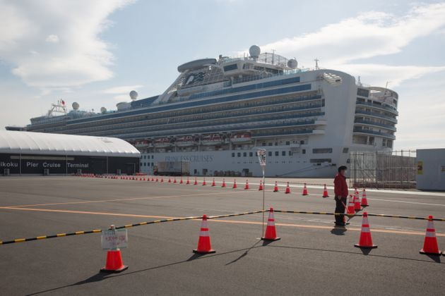 A guard stands at a restricted area in front of the Diamond Princess cruise ship in