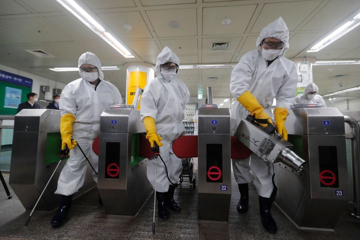 Workers wearing protective gears spray disinfectant as a precaution against the new coronavirus at a subway station in Seoul,