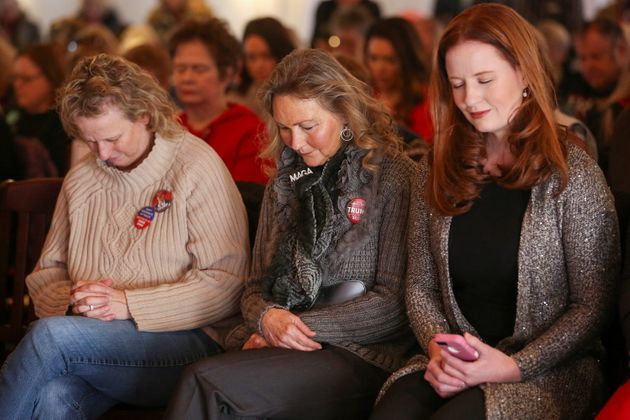 Supporters bow their heads in prayer at a Women for Trump bus tour stop in Sioux City, Iowa, on Jan.