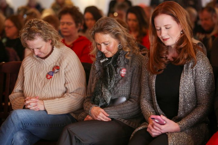 Supporters bow their heads in prayer at a Women for Trump bus tour stop in Sioux City, Iowa, on Jan. 16.