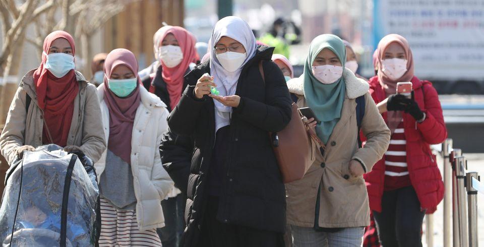 29일 서울 광화문 네거리를 찾은 외국인 관광객들이 마스크를 쓰고 손 세정제로 손을 세척하고
