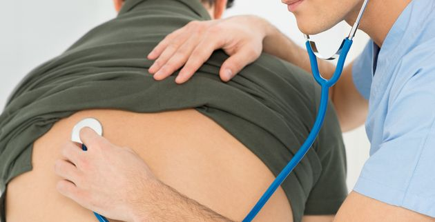 Young Male Doctor Checking Patient With Stethoscope In