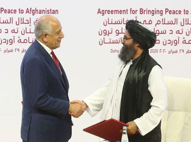 Zalmay Khalilzad côté américain et le chef politique des insurgés afghans,...