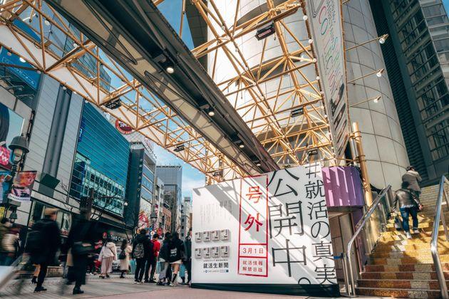 渋谷に登場した巨大広告。備え付けのラックに入れられた号外は誰でも手に取れる。