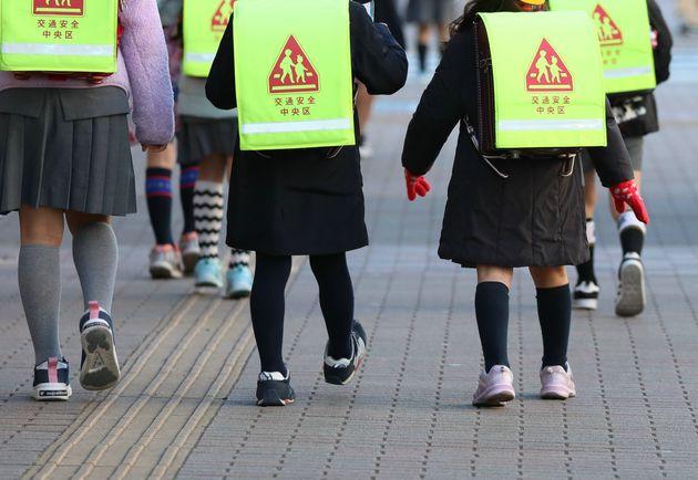 登校する小学校の児童ら。政府は週明けから臨時休校とするよう呼び掛けている。