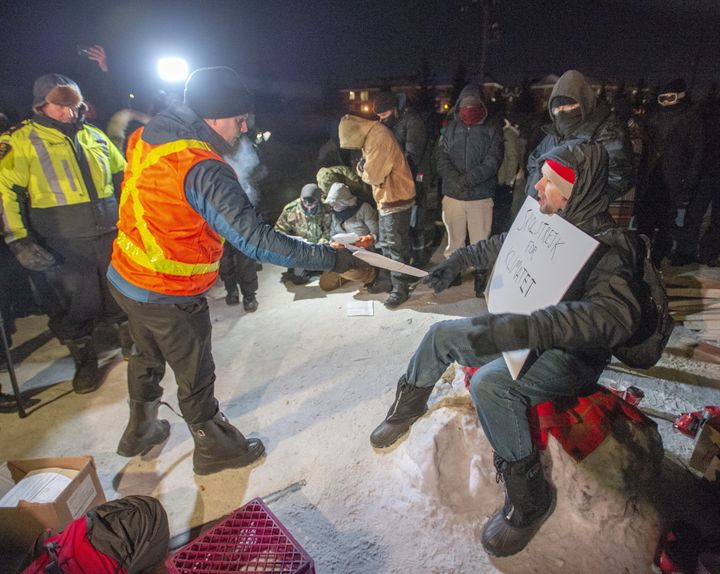 Police serve an injunction to protesters at a rail blockade in St-Lambert, south of Montreal on Feb. 20, 2020.