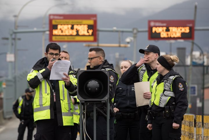 A Port Authority security guard is flanked by police officers as he reads out an injunction against protesters in Vancouver, on Feb. 25, 2020.