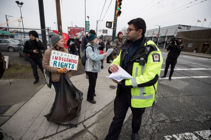 A Port Authority security guard hands out copies of an injunction to protesters in Vancouver, on Feb. 25, 2020.