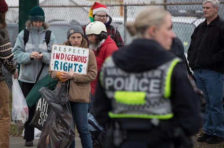 A woman holds a sign as people watch from the sidewalk as police officers prepare to enforce an injunction in Vancouver, on Feb. 25, 2020.
