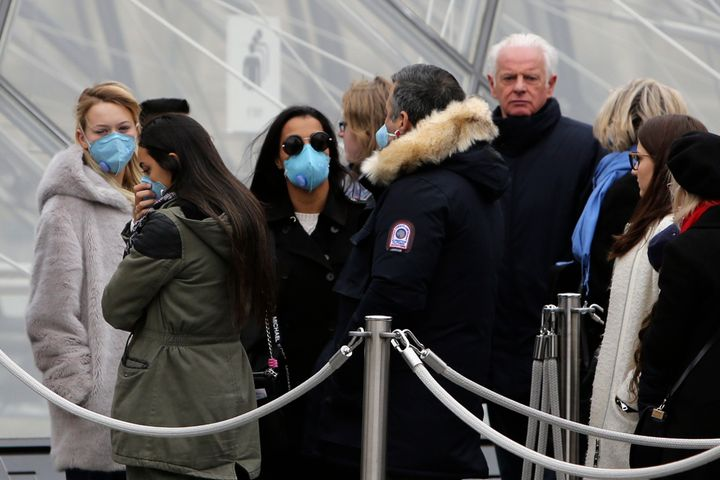 Tourists, some wearing a mask, queue to enter the Louvre museum Friday, Feb. 28, 2020 in Paris. The world is scrambling to ge