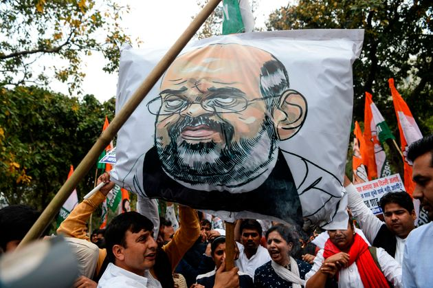 Youth Congress activists shout slogans next to an effigy of Home Minister Amit Shah during a protest...