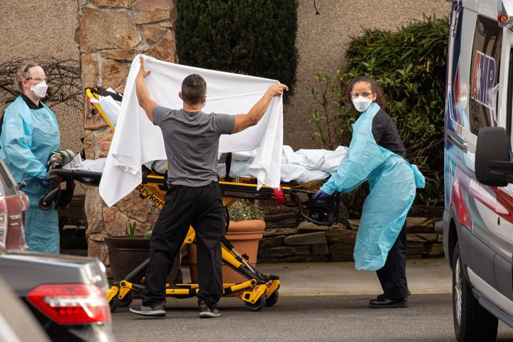 Healthcare workers transport a patient on a stretcher into an ambulance at Life Care Center of Kirkland on February 29, 2020