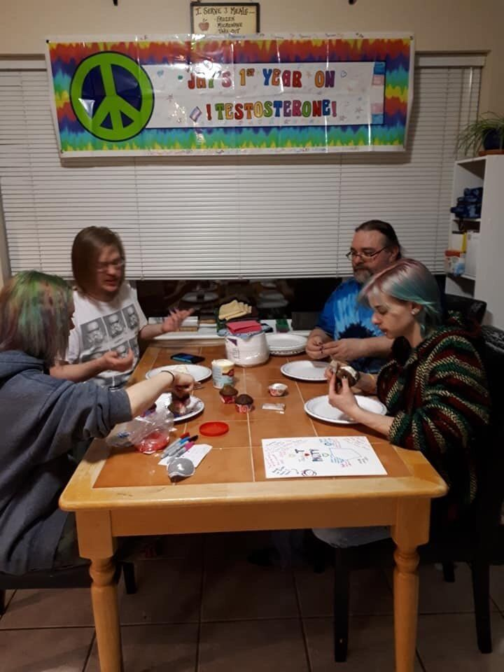 """The Scott family and some friends decorate cupcakes for the anniversary party. The banner above the table reads, """"Jay's 1st year on testosterone."""""""