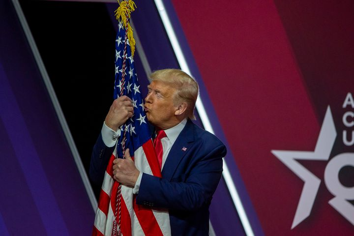 Trump kisses the U.S. flag at the annual Conservative Political Action Conference in National Harbor, Maryland, on Feb. 29, 2020.