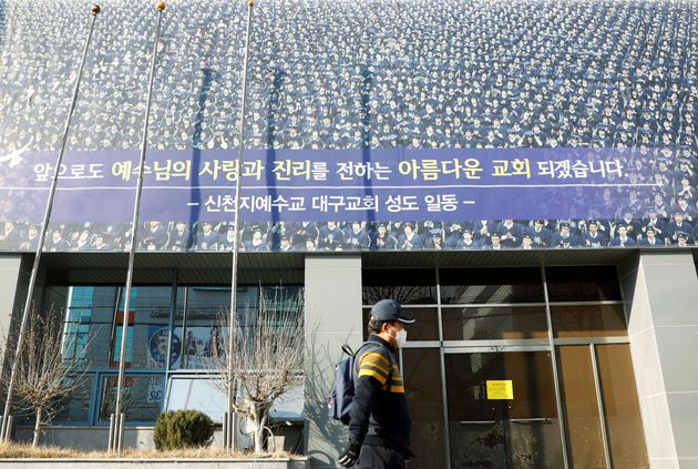 A man wearing a mask walks past a branch of the Shincheonji Church of Jesus amid a rise in confirmed...