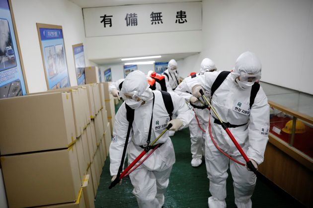 South Korean soldiers wearing protective gear sanitize inside the facility of a city hall after the rapid...