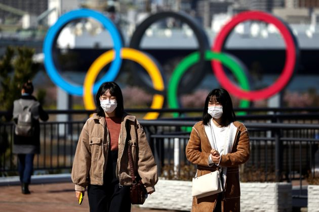 People wearing protective face masks in front of the Giant Olympic rings at the waterfront area at Odaiba...