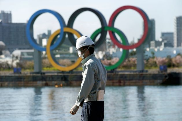 A masked man works at a construction site with the Olympic rings in the background on Tuesday, March...