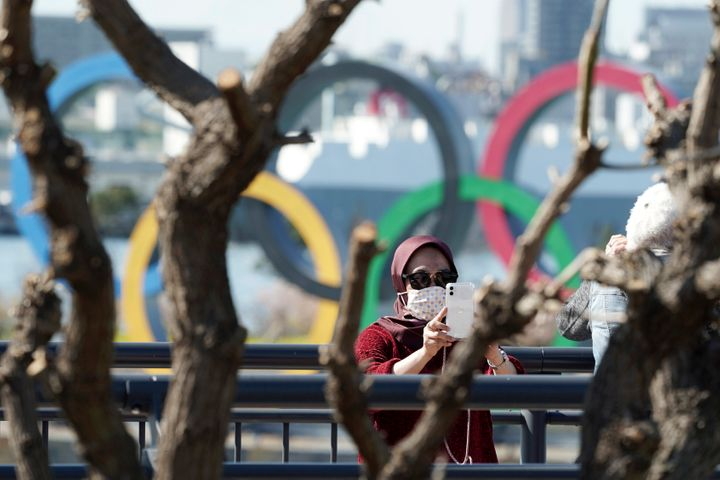 A tourist wearing a protective mask takes a photo with the Olympic rings in the background in Tokyo on Tuesday. The spreading