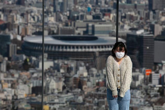 A woman with a mask pauses for photos on Shibuya Sky observation deck as the New National Stadium, a...