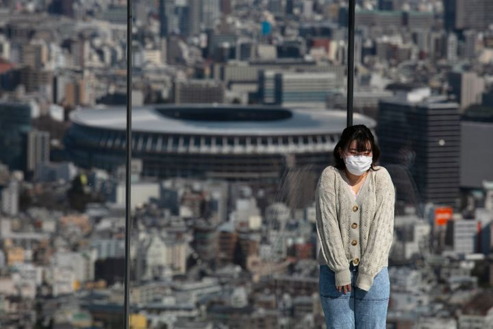 A woman with a mask pauses for photos on Shibuya Sky observation deck as the New National Stadium, a venue for the opening an