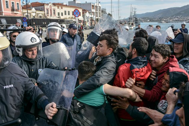 Migrants scuffle with Grek police at the port of Mytilene after locals block access to the Moria refugee...