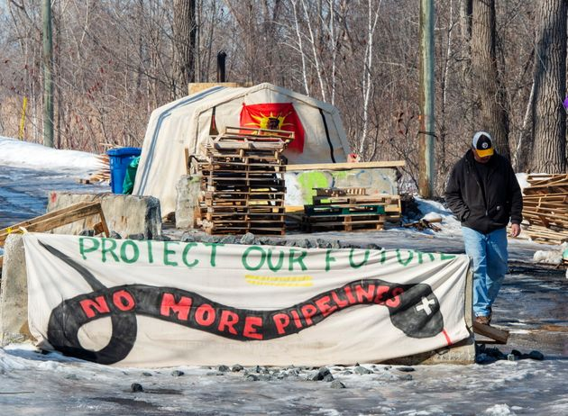 A member of the Mohawk community stands near the blockade of the commuter rail line on March 3, 2020...