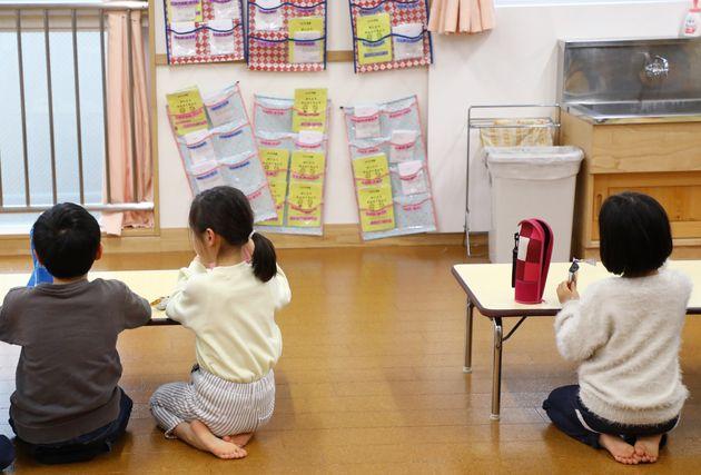 学童保育室での飛沫感染を防ぐため、テーブルの間隔を空け、壁に向かっておやつを食べる子どもたち=3月2日、東京都足立区の千住あずま住区センター