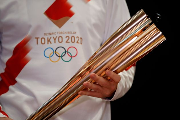 Greek singer Sakis Rouvas wears the uniform of the torch relay runners as he holds the torch of the 2020...
