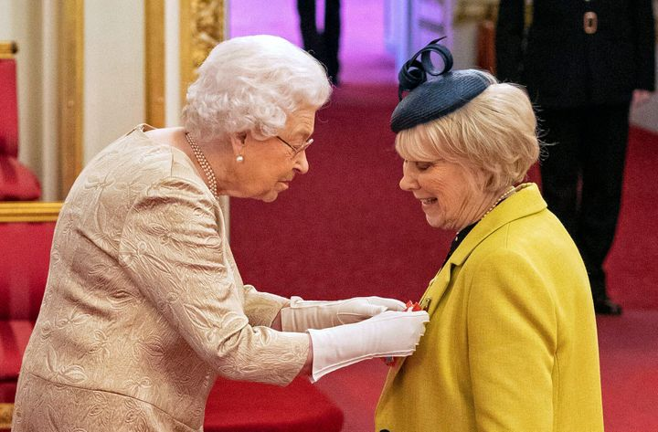 Queen Elizabeth II wore gloves as she awarded honors during an investiture ceremony at Buckingham Palace in London on Tuesday