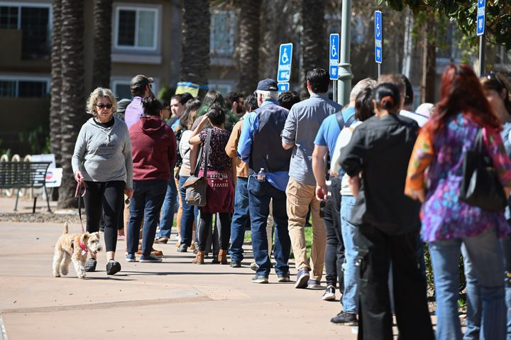 A woman walks her dog past a long line of voters waiting to cast their ballot in the presidential primary at the Buena Vista