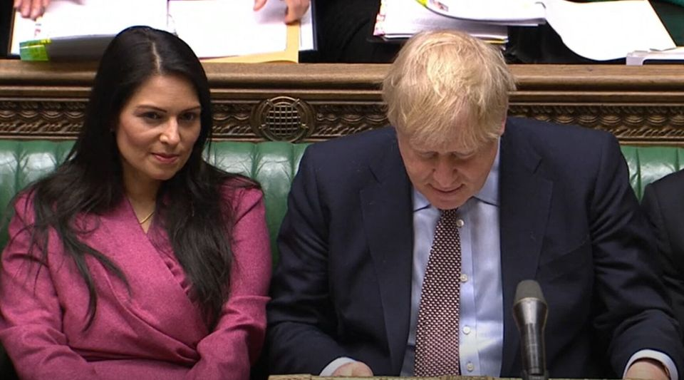Patel sat next to Johnson as he defended her at PMQs on